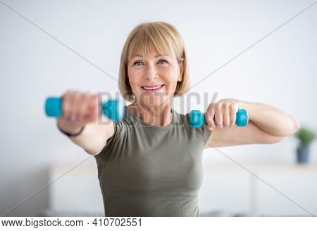 Portrait Of Positive Senior Lady Exercising With Dumbbells At Home During Covid-19 Quarantine. Happy