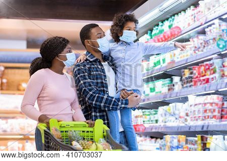 Shopping During Covid-19 Outbreak. Young Black Family Wearing Disposable Masks While Buying Dairy Pr