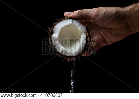 Isolated Coconut On A Black Background. Coconut Milk Is Poured From Half A Coconut. Half Of A Coconu