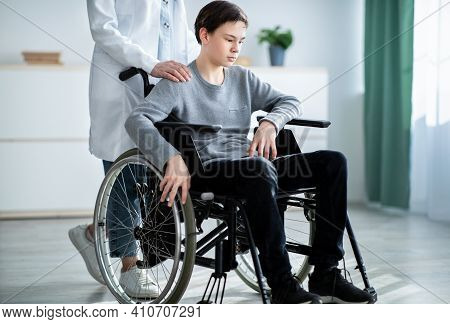 Impaired Teenager In Wheelchair Suffering From Depression, Doctor Or Nurse Taking Care Of Him At Hom