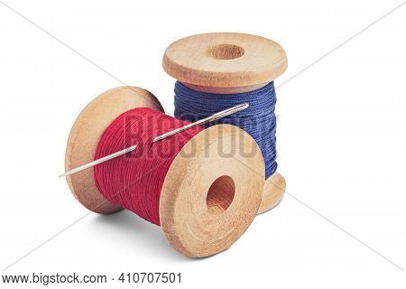 Sewing Needle And Colorful Sewing Thread On Wooden Spool On Isolated White Background