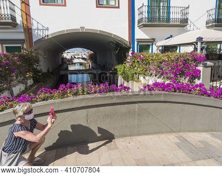 Puerto De Mogan, Gran Canaria, Canary Islands, Spain December 18, 2020: Senior Woman In Face Mask Ta