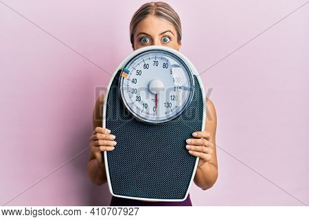Beautiful blonde woman holding weight machine to balance weight loss celebrating crazy and amazed for success with open eyes screaming excited.