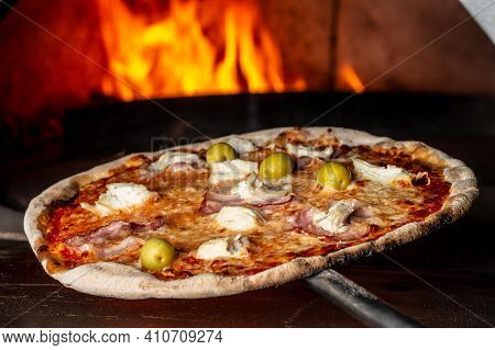 Restaurant Chef Takes Pizza From Oven. Preparing Traditional Italian Pizza. Chef Holding Shovel For