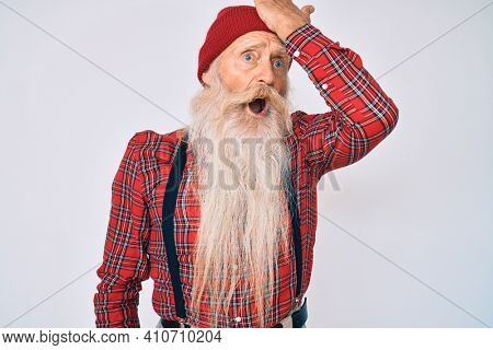 Old senior man with grey hair and long beard wearing hipster look with wool cap surprised with hand on head for mistake, remember error. forgot, bad memory concept.