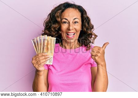 Middle age hispanic woman holding norwegian krone banknotes pointing thumb up to the side smiling happy with open mouth