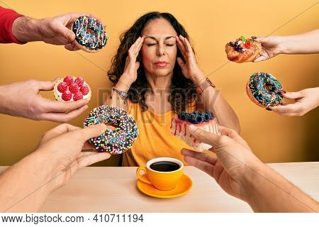 Beautiful middle age woman drinking a cup of coffee around pastries with hand on head, headache because stress. suffering migraine.