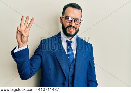 Young man with beard wearing business suit and tie showing and pointing up with fingers number three while smiling confident and happy.