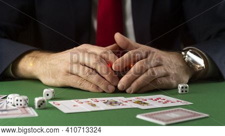 Businessman At Green Gaming Table With Game Chips, Cards And Dice Playing Poker And Blackjack In Cas