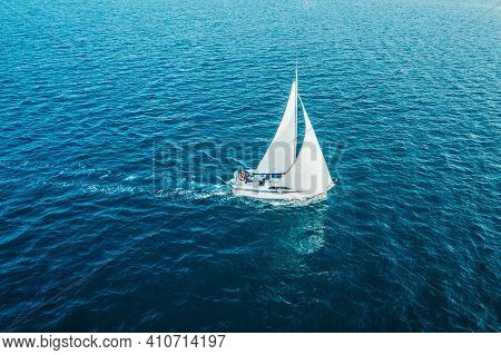 Sailing Ship Yacht With White Sails At Opened Sea. Aerial - Drone View To Sailboat In Windy Conditio