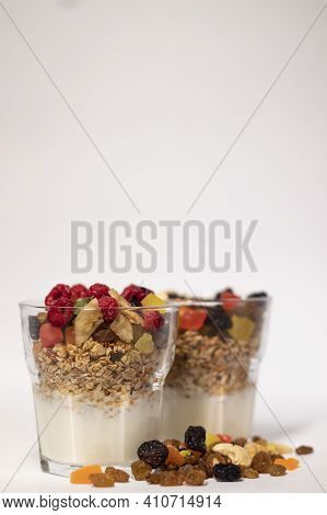 Muesli Dessert In Glass With Yogurt And Candied Or Dried Fruits With Raspberries On Top, Isolated On