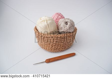 Yarn In A Knitted Basket On A White Background With A Hook. Yarn Of Different Colors. The Concept Of