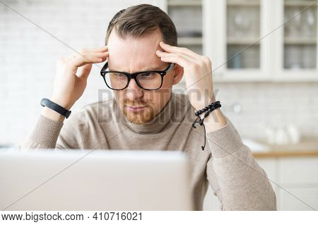 Nervous Business Man Sitting At Laptop Holding Hands To Temples, Thinking Over Problem Trying To Foc