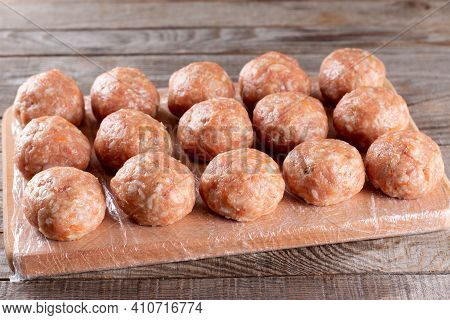 Side View Closeup On Raw Semi-finished Frozen Meatballs On The Wooden Board With Rice, Onion And Mea