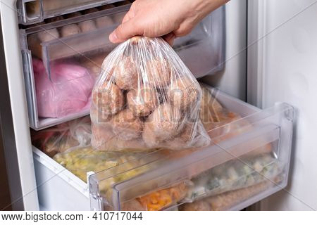 Frozen Food In The Refrigerator. Plastic Bag With Meatballs In Refrigerator, Closeup
