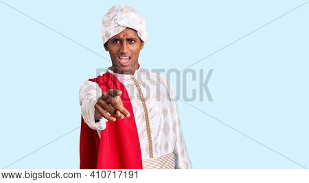 African handsome man wearing tradition sherwani saree clothes pointing displeased and frustrated to the camera, angry and furious with you