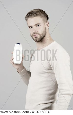 Man Confident Face Holds Shampoo Bottle, Grey Background. Guy With Bristle Holds Bottle Shampoo, Cop