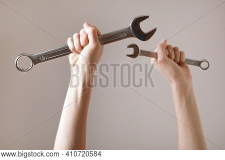 Two Spanners In The Women's Hands. Hands Holds A Wrenches On A Gray Background. Combination Wrench.