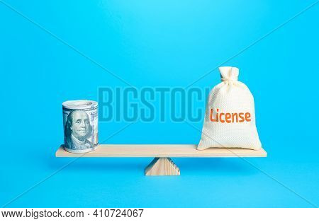 Dollars Bundle And A Bag With Word License On Scales. Estimating The Value Of Copyrights And Patents