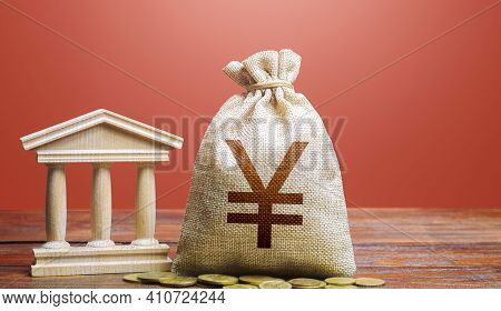 Yuan Or Yen Money Bag And Bank / Government Building. Monetary Policy. Tax Collection And Budgeting.