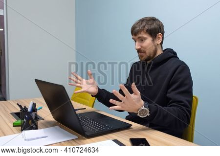 Emotional Young Man Working In The Office On A Laptop. Frustrated Man Confused By Unexpected Error O