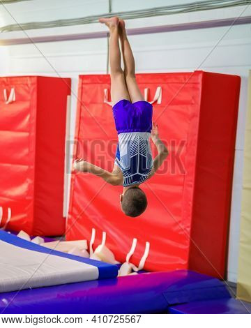 A Young Guy Performs A Jump Somersault, In Training. Gymnastics.