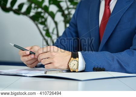Trader Man In Suit Sitting In Office And Analyzing Report. Business And Paperwork Concept. Close Up