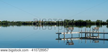 An Inviting Boat Dock Is Reflected In The Glassy Water Of Lake Irving, The First Lake On The Mississ