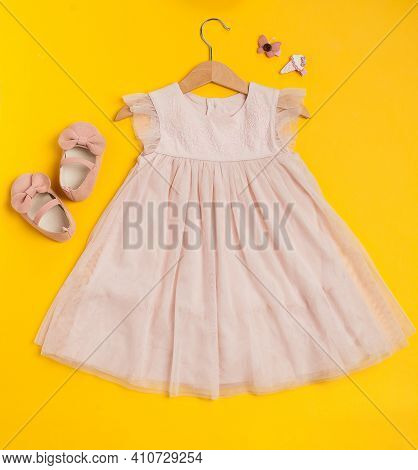Childrens Festive Outfit On A Yellow Background. Cute Baby Pink Dress With Shoes And Hairpins.