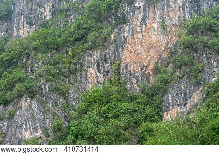 Guilin, China - May 10, 2010: Along Li River. Closeup Of Gray-beige Rock Cliff Partly Covered With G