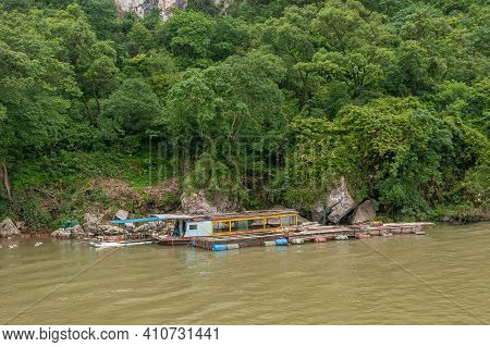 Guilin, China - May 10, 2010: Along Li River. House Boat And Barge Docked At Forested Shoreline. Blu