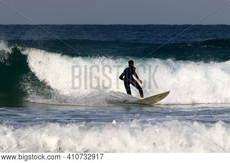 Surfing High Waves In The Mediterranean Sea In Northern Israel. Gliding Along The Crest Of A Large S