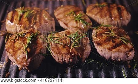 Delicious Juicy Meat Steak Cooking On Grill. Prime Beef Fry On Electric Roaster, Rosemary, Black Pep