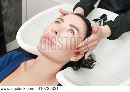 Professional Hairstylists Hands Wash Long Hair Of Brunette Woman With Shampoo In Sink For Shampooing