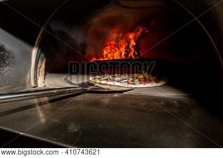 Traditional Way Baked Wood Fired Oven Italian Pizza Bakery Pizzeria. Restaurant Chef Takes Pizza Fro