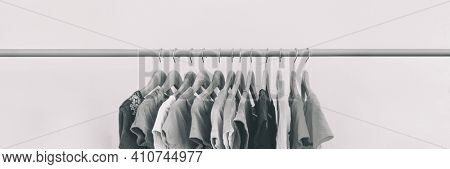 Clothing rack of women's closet organizing clothes for spring cleaning or fashion store outlet sale. Panoramic black and white style banner.