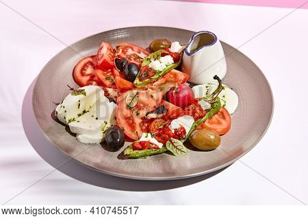 Tomato, olives and mozzarella salad . Restaurant appetizer plate on white table with pink wall. Day sunlight with hard shadow of fern palm leaves. Summer or spring restaurant food concept