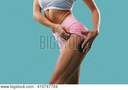 Close-up Side Shot Of A Slim Fit Body Of A Young Muscular Build Woman Doing Massage On Her Thigh Wit