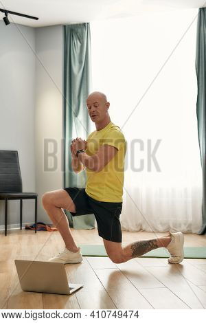 Male Trainer Performs Exercising At Home. Trainer 48 Years Old In Sportswear Performing Squatting An