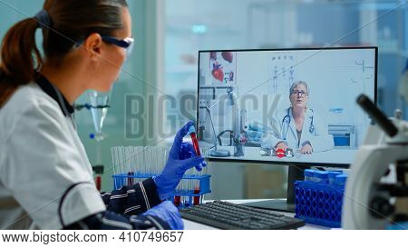 Physician Doctor Offering Medical Online Advices To Chemist Student Using Pc. Scientist Holding Bloo