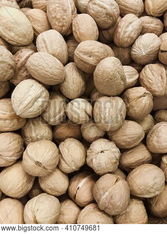 Natural Walnut Background. Background Filled With Walnuts In Shell. Close-up Vertical Photo Of A Wal
