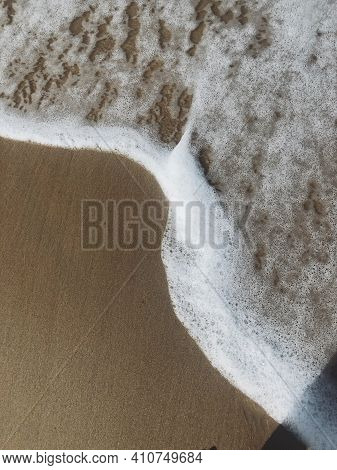 The Sandy Coast Of The Sea On Which A Small Wave Rushed. Autumn Sea. Rolling Small Foam Wave On The