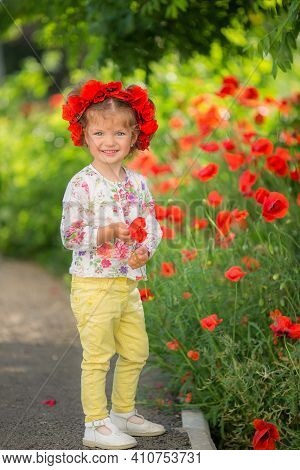 Portrait Of A Beautiful Little Girl Having Fun In Field Of Red Poppy Flowers In Spring. Lovely Smili