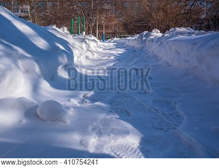 A clear path with snow drifts on both sides. Winter footpath. Winter in the city.