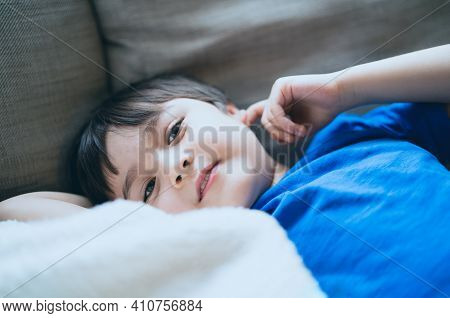 Close Up Face Of Kid Looking At Camera With Smiling, A Happy Boy Lying On Sofa Relaxing On Weekend,