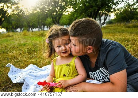 Little Brother Playing With His Baby Sister. Kissing Her And Smiling. Leisure Outdoor Summer Picnic.