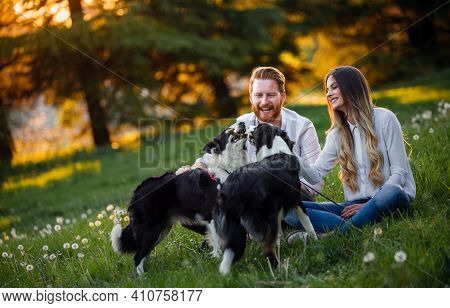 Happy Young Couple Walking, Playing With Dogs In A Park