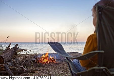 Family Local Getaway. Kid Sitting On The Touristic Armchair And Looking At Fire Before Overnight At