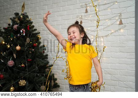 A Joyful Child Catches Tinsel. A Bright Childrens Holiday. A Child In A Yellow T-shirt Catches A Ser