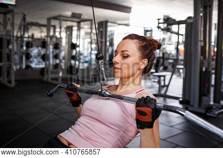 Young Sporty Woman Training Her Lats And Biceps